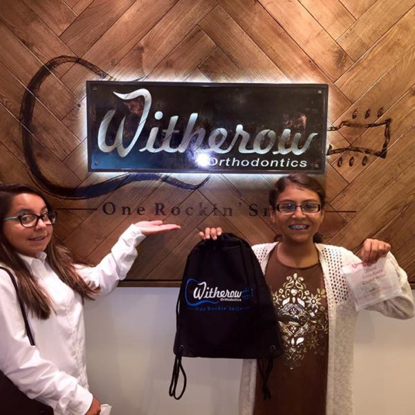Happy patients smiling in front of the Dr. Witherow sign