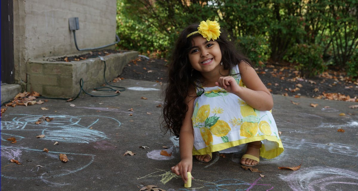 A smiling girl plays with chalk
