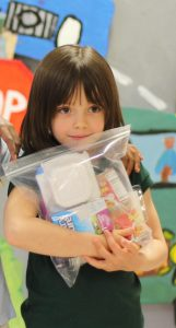 A girl tightly clutches a BackPack she received from Second Harvest